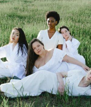Un groupe de femmes habillées en blanc allongées dans l'herbe (photo prétexte de banque d'image)