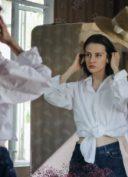 Une jeune femme essaye un jean face à un miroir