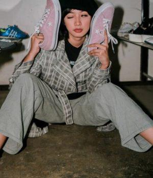 Assise au sol, une femme essaye plusieurs paires de chaussures