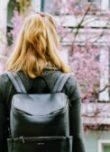 Une femme avec un joli sac à dos se tient face à un cerisier en fleur