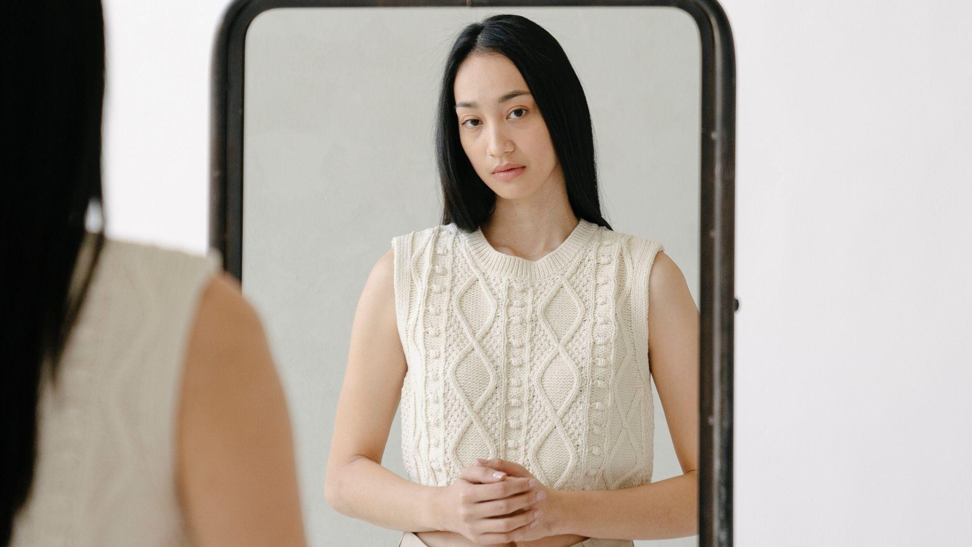 Femme debout devant un miroir