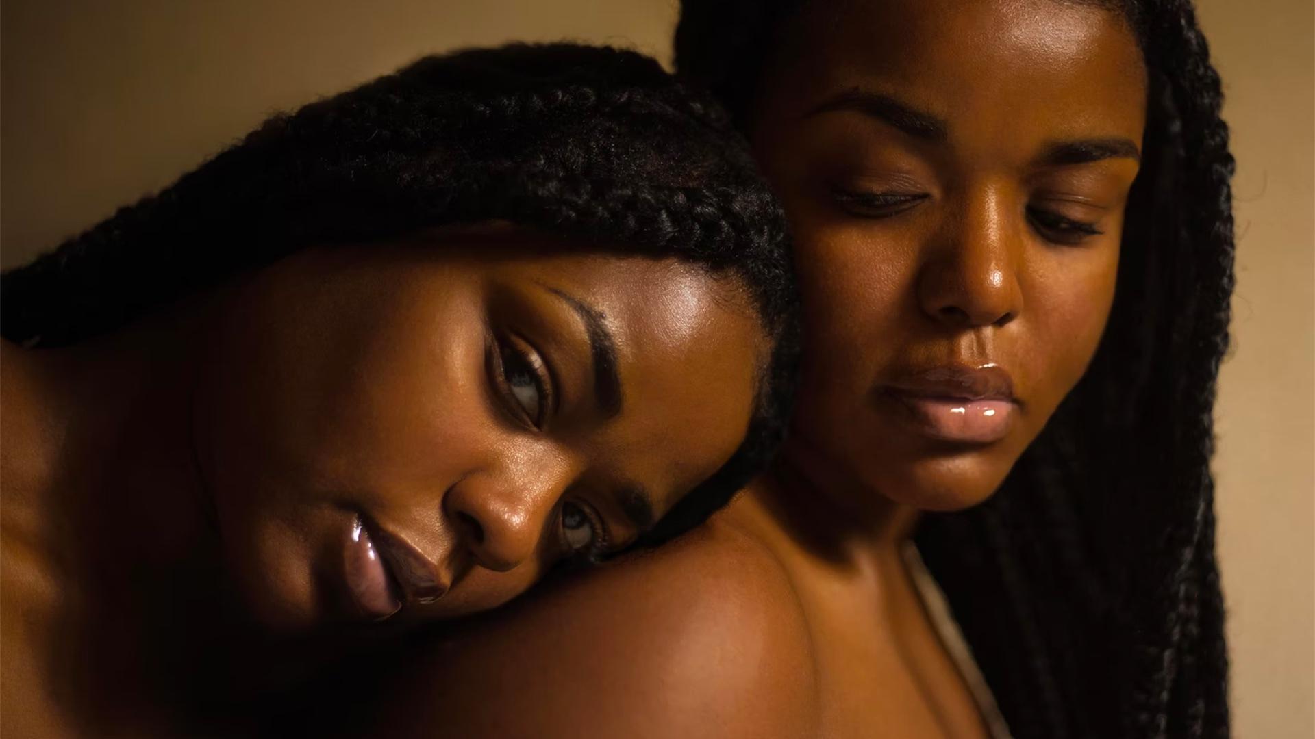 Deux femmes noires, l'une pose sa tête sur l'épaule de l'autre.